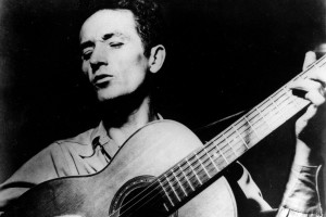 "FILE - This undated file photo shows folk singer Woody Guthrie playing his guitar and singing. Guthrie's writings, recordings and artwork will land in his native state after an Oklahoma foundation bought the collection, with plans for a display that concentrates on his artistry rather than the populist politics that divided local opinion over the years. Guthrie, known for the anthem, ""This Land is Your Land"" and his songs about the poor and downtrodden, is remembered mostly as a musician, composer and singer, but was also a literary figure and an artist, said Bob Blackburn, executive director of the Oklahoma Historical Society.   (AP Photo/File)"